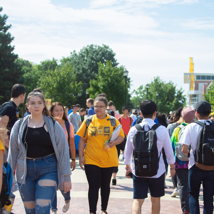 Students walking across campus on a sunny day.