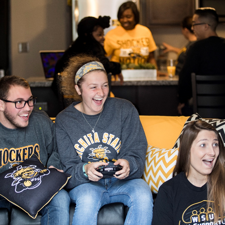 Students laugh while playing video games within the living room of an apartment at The Flats.