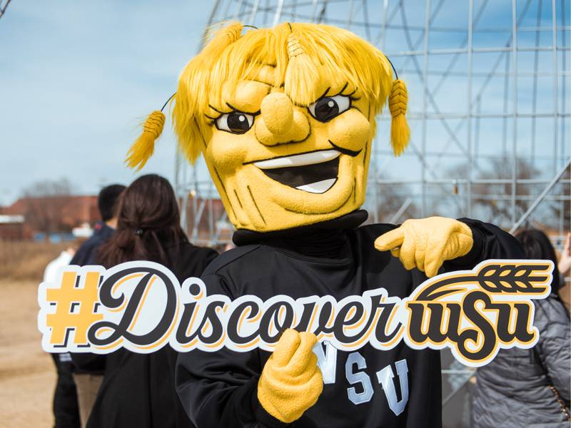 Wu holding up a Discover WSU sign