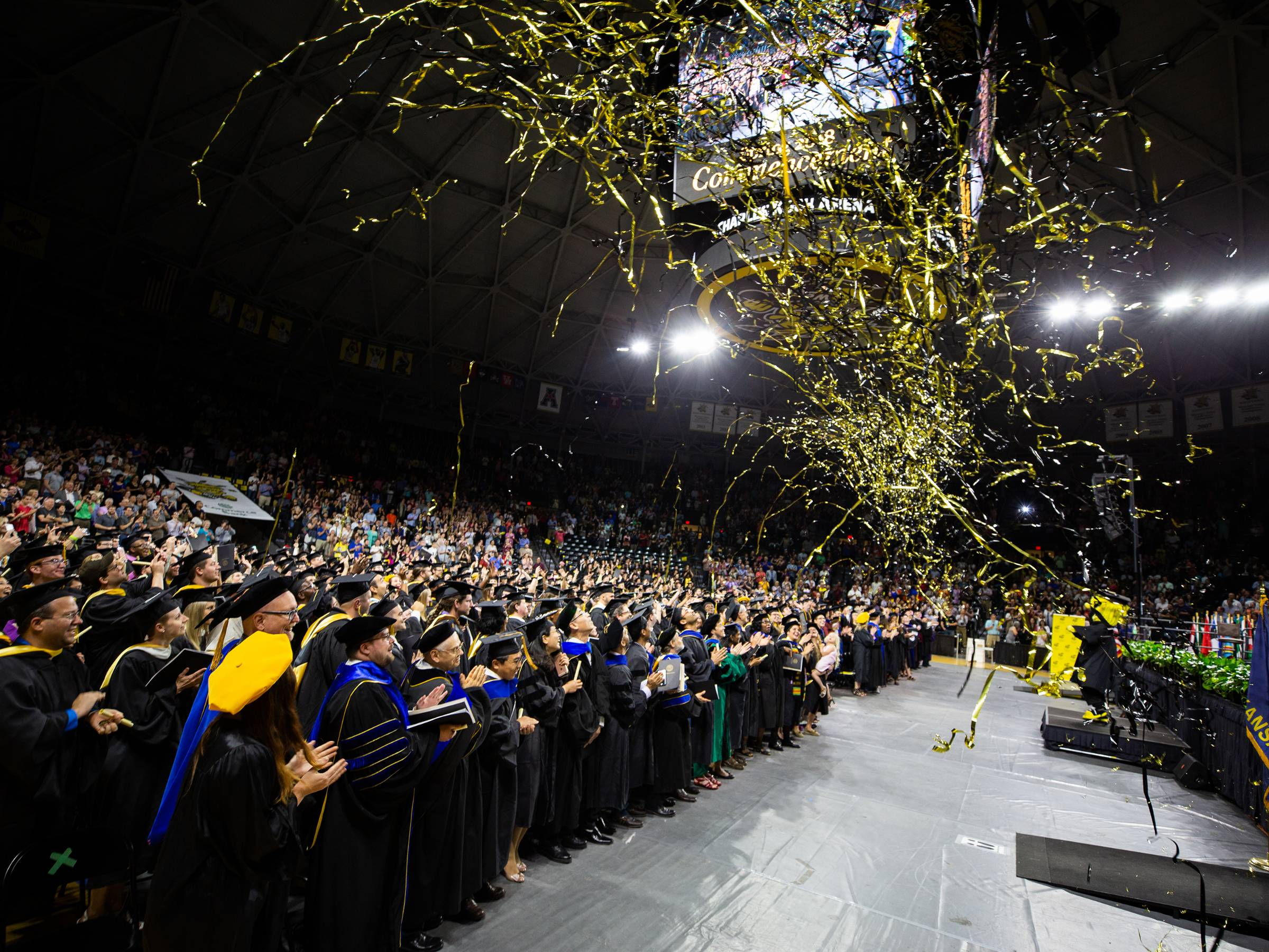 Graduates on the commencement floor at Charles Koch Arena