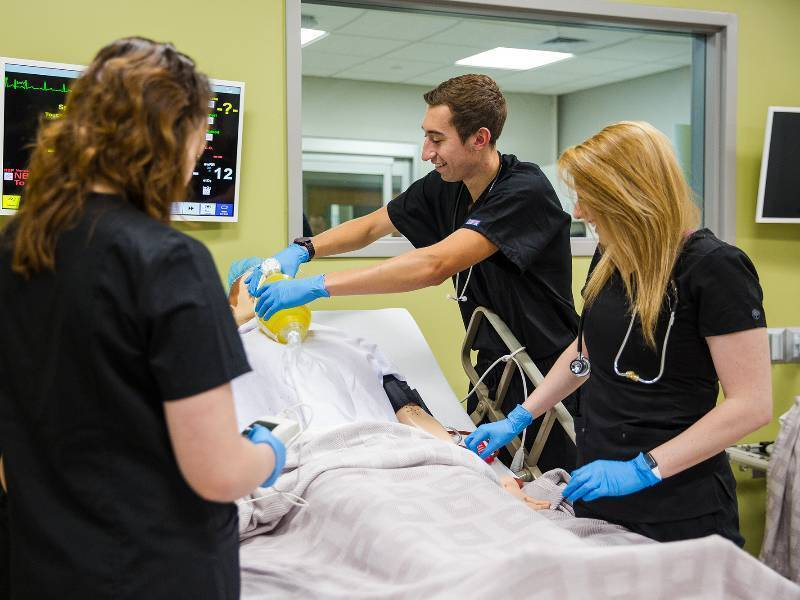 Students work with medical mannequins