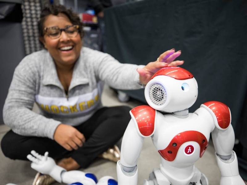 Female student with Robot in Robotics lab.
