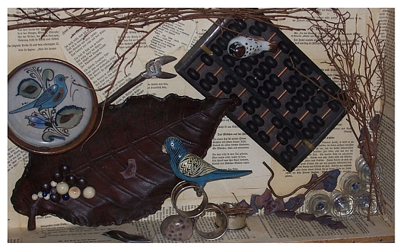 Photo displaying an art piece featuring ceramic bluebirds, an abacus, and various twigs on a backdrop of book pages.