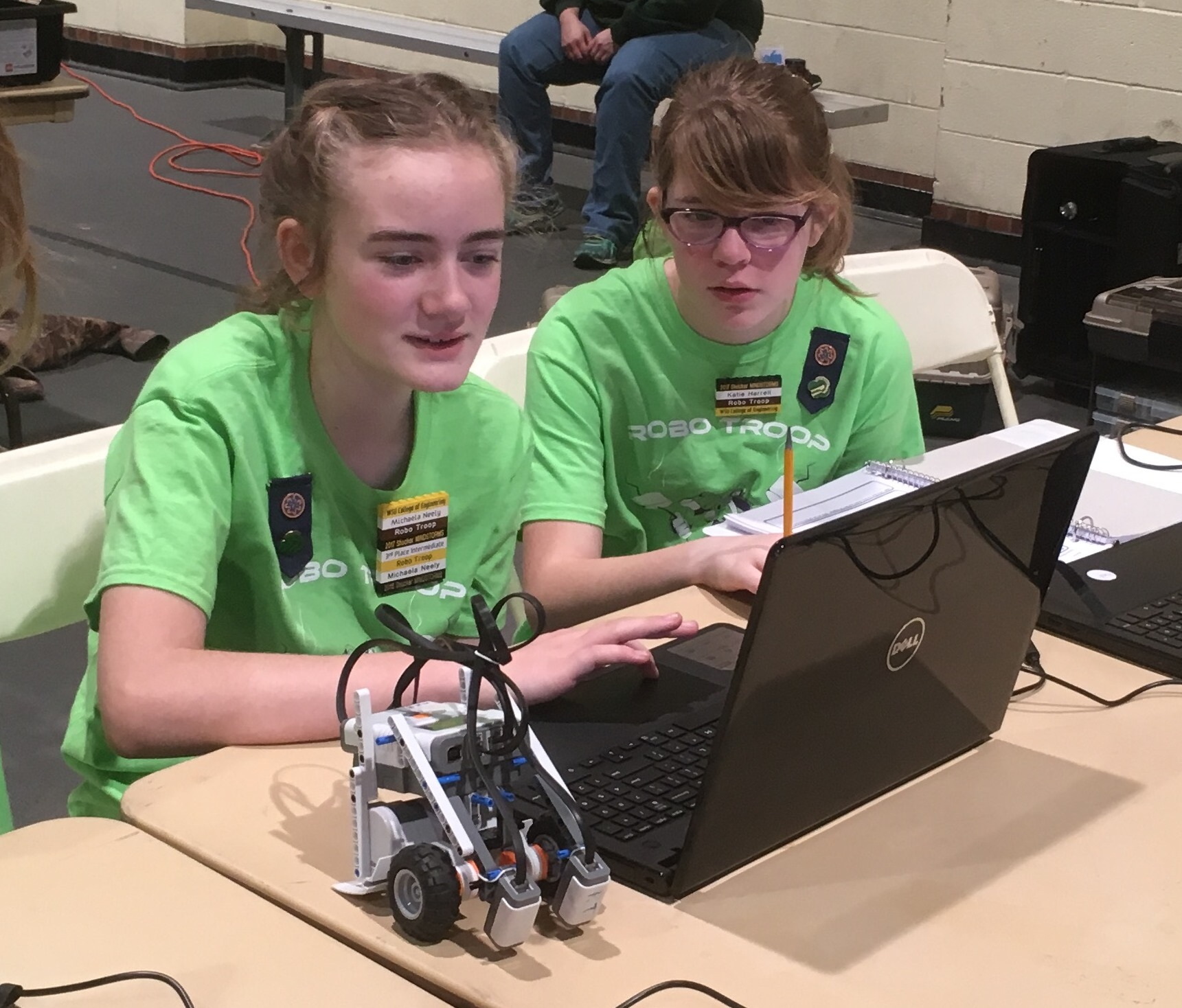 Members of the Girls Scouts of the Kansas Heartland's Robo Troop MINDSTORMS team modify the program on their LEGO robot between competition runs during the 2017 challenge.