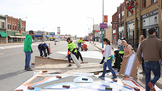 Students and the Wichita community work together to add a vibrant street mural to the Douglas Design District.