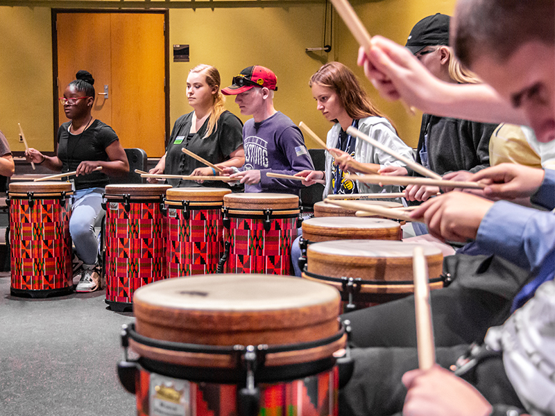 Students use drums during a performing arts class.
