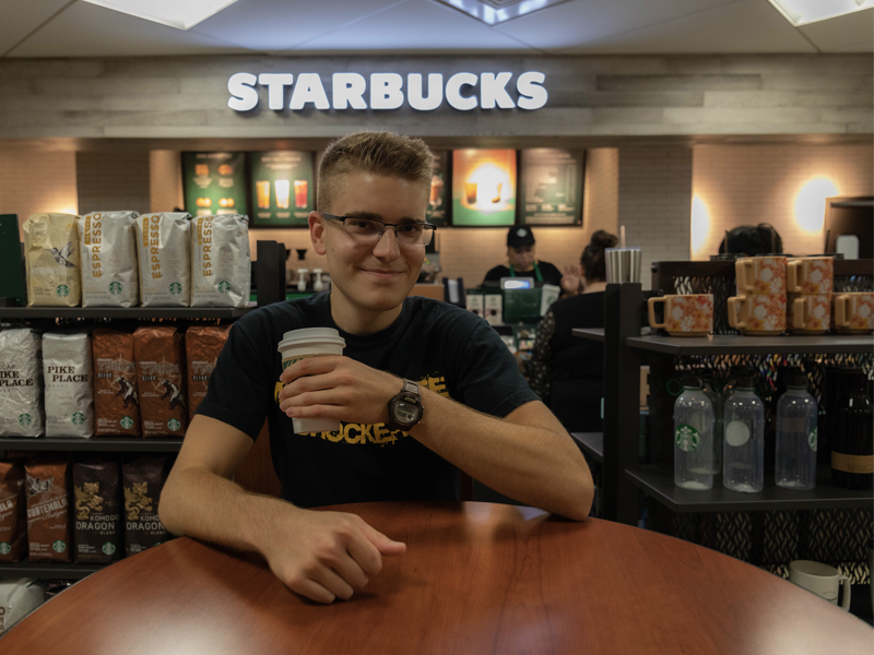 Andrew Martin, marketing intern, enjoys a cup of coffee at the Starbucks in the Rhatigan Student Center.