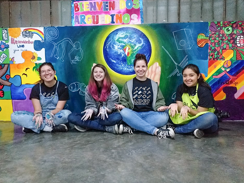 Celine, Bishop, Haley and Lily sit in front of their mural in Peru.