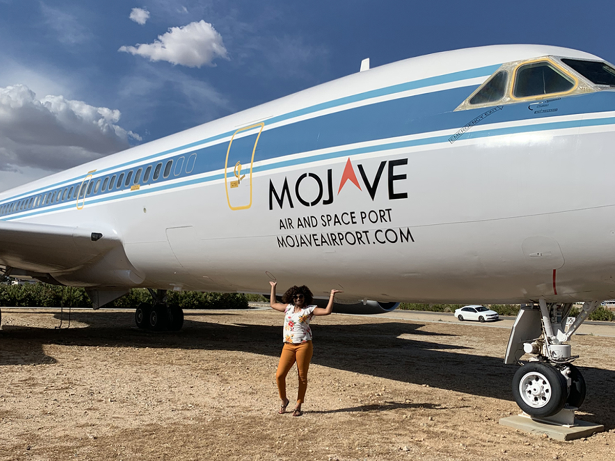 Khristian Jones stands in front of the Convair 990 jet parked in front of Mojave Air and Space port in California.