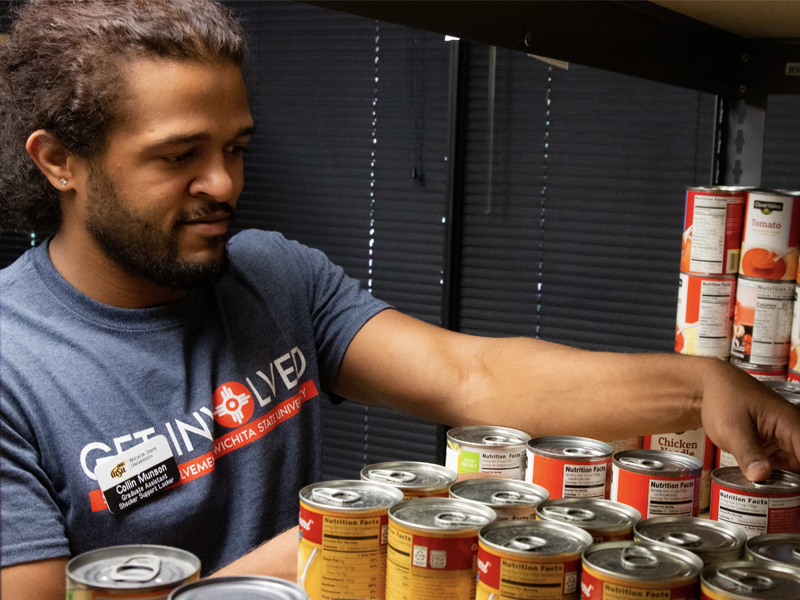 Collin Munson organizes cans inside the food locker.