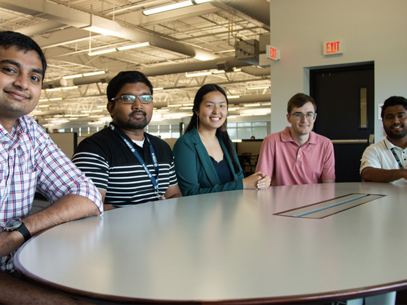 From left to right: Alok Dand, Suveen Emmanuel, Angelique Banh, Shane Grode and Pardhiv Marella sit at a table in the Airbus Wichita facility