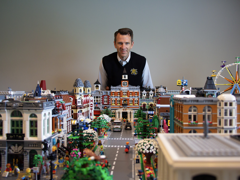 Dennis Livesay stands behind his LEGO city, overlooking the city hall and main boulevard