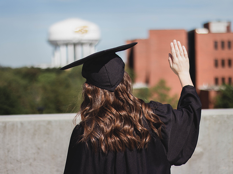 Maddie Harris waves goodbye to campus as she graduates