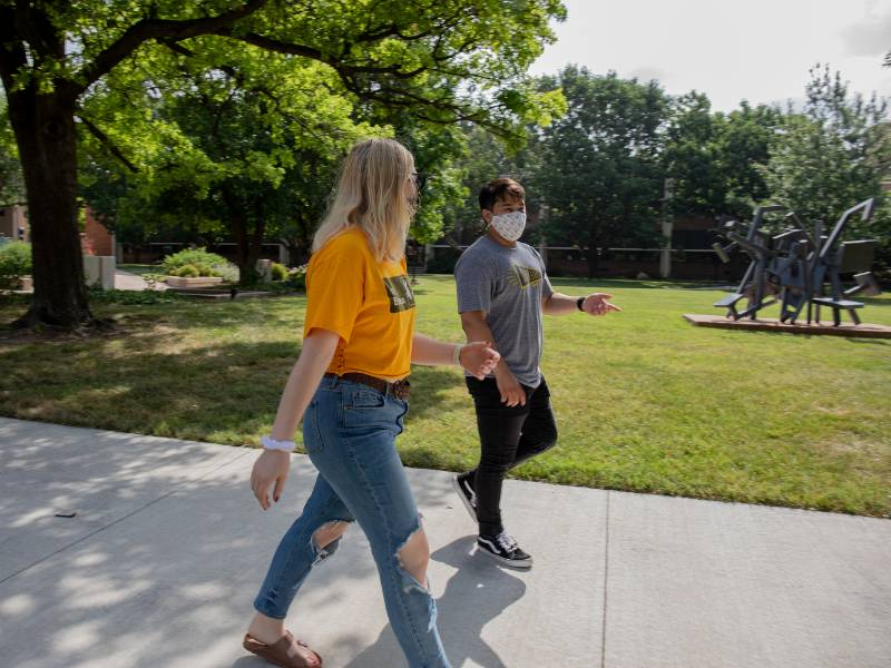 Students walking with masks on campus