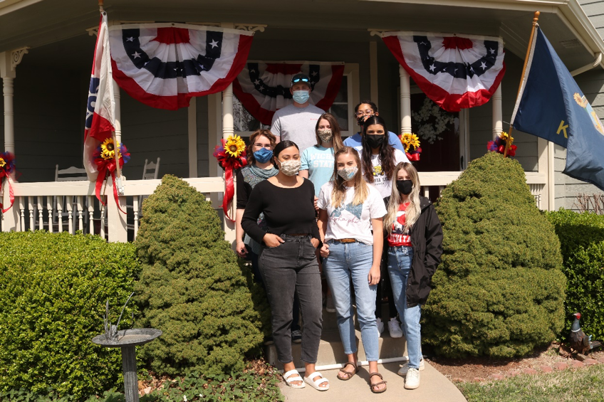 Students standing in front of a decorated porch