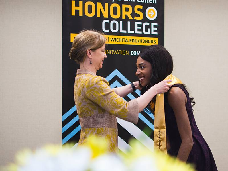 Honors College Dean Engber awards a student their honors stole for graduation