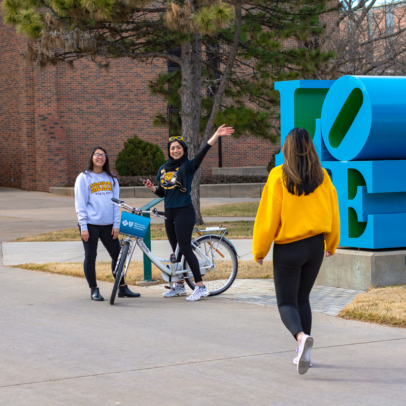 girls with bikes on campus