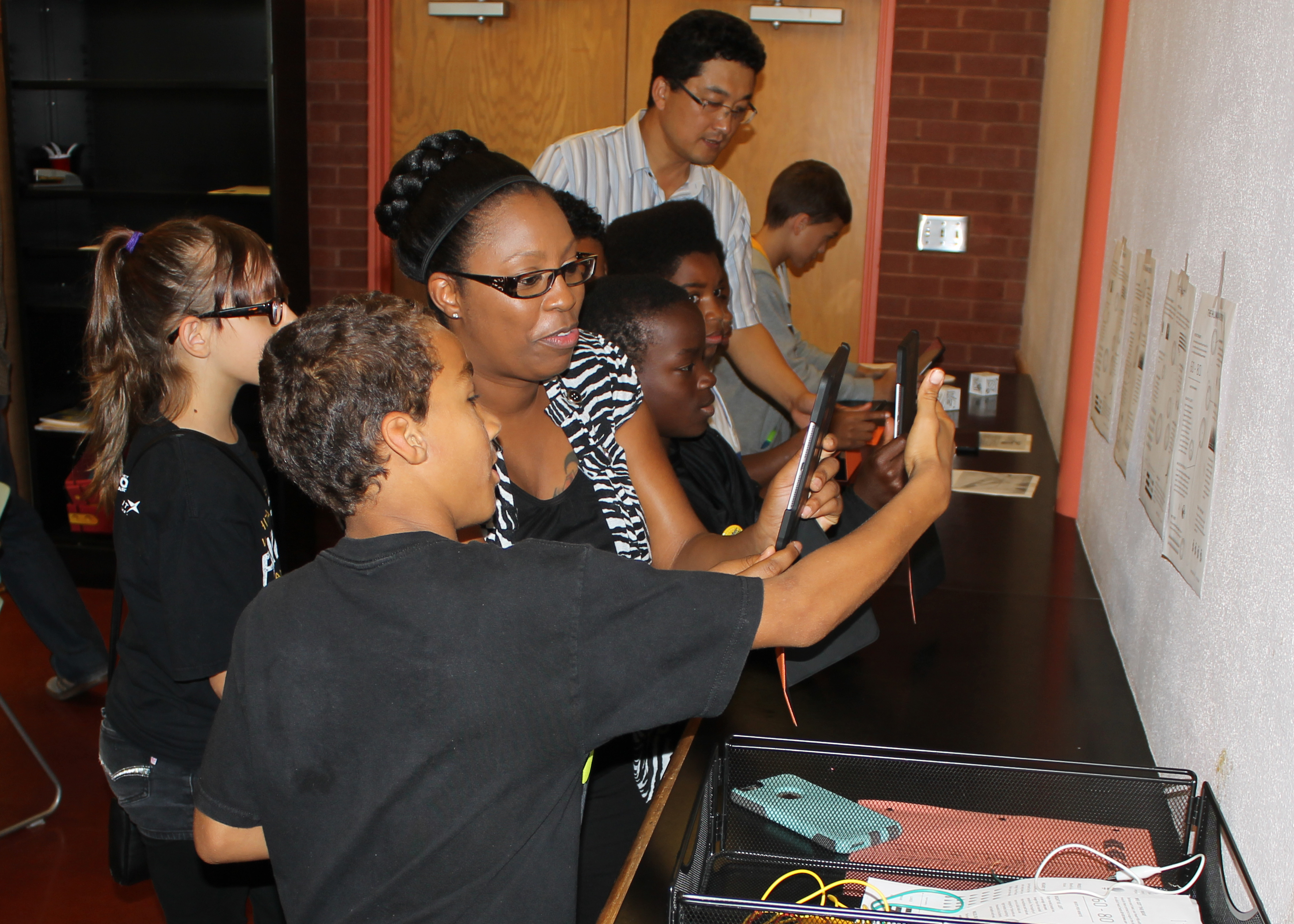 Students and a teacher look through a device.
