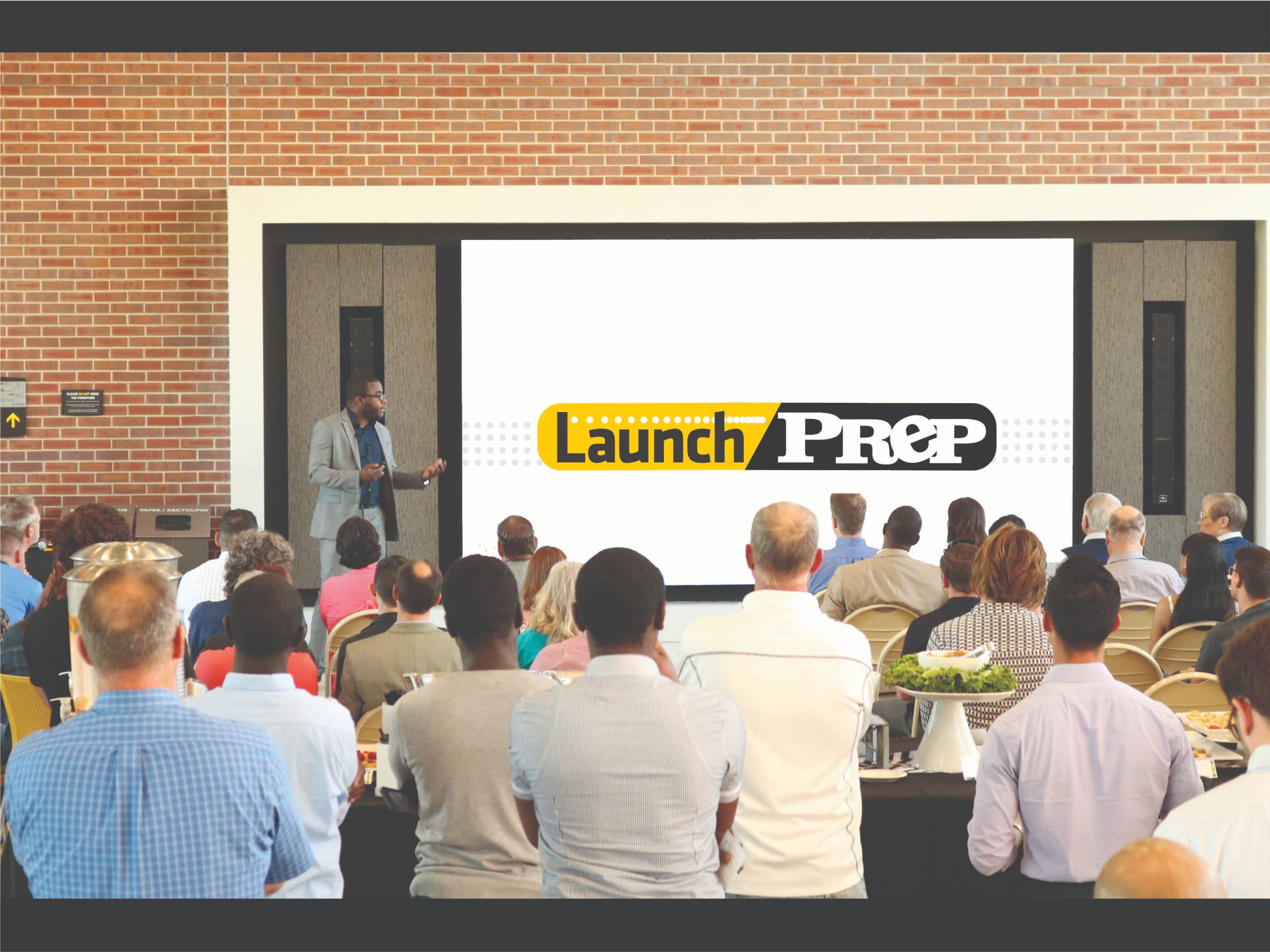A man giving a presentation to an audience with launchprep logo.