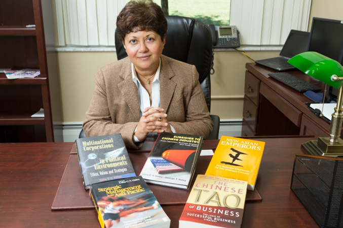 Usha Haley at a desk, with a series of books.