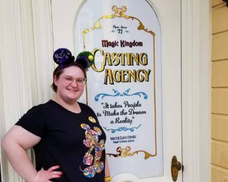 Woman in Mickey Mouse ears poses next to Casting Agency sign at Walt Disney World Resort