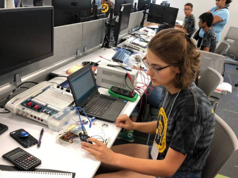 A young woman works on an Arduino computer