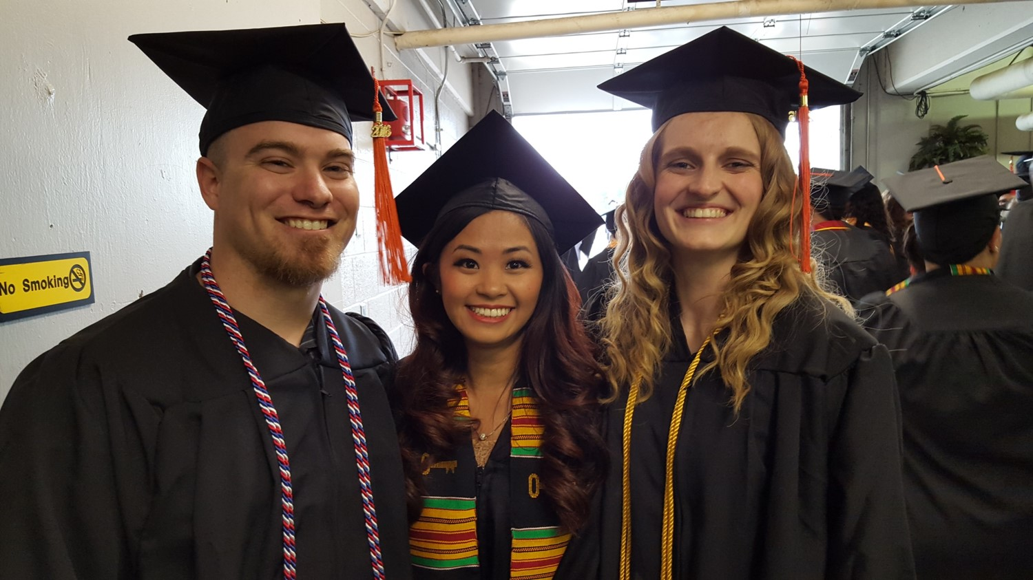 Photo of three smiling Engineering students during graduation.