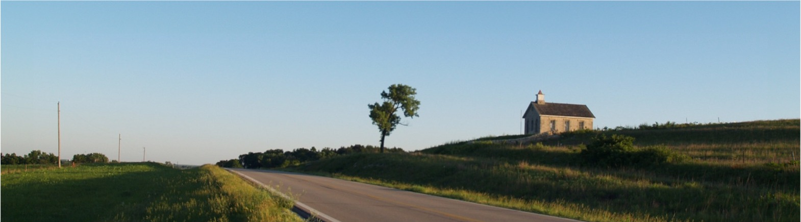 Jay Price homepage header - a solidary home along a highway under a clear blue sky.