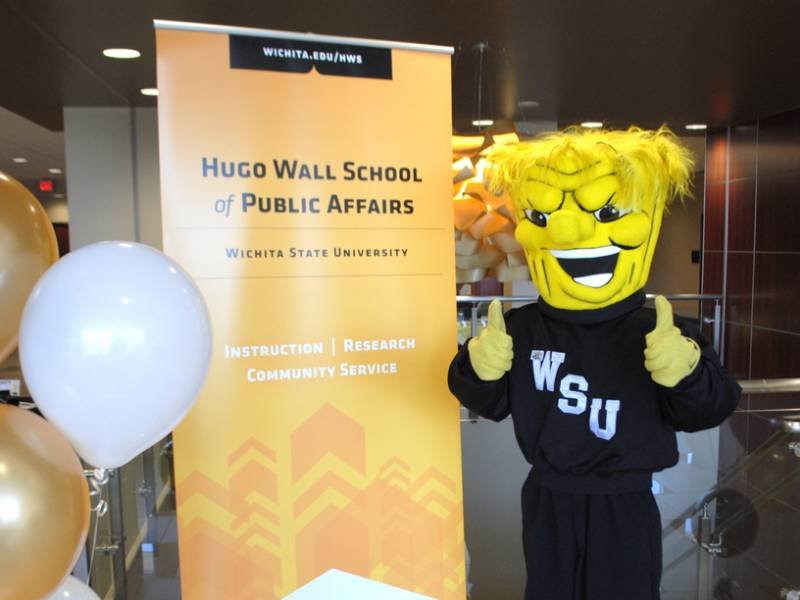 Wu gives a thumbs up at a Hugo Wall sign