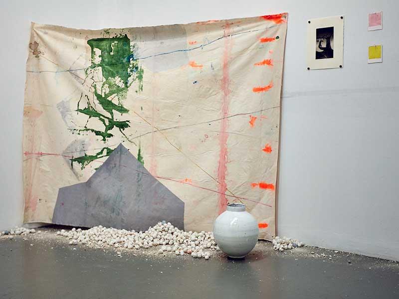 Photograph of a student installation in the ProjectSpace gallery: a large abstract painting on a piece of unstretched canvas hangs across the cover of a wall behind a white ceramic vase, and white ceramic objects that look like rocks. A black-and-white photograph and two small paintings, one pink and one yellow, hang by the canvas.