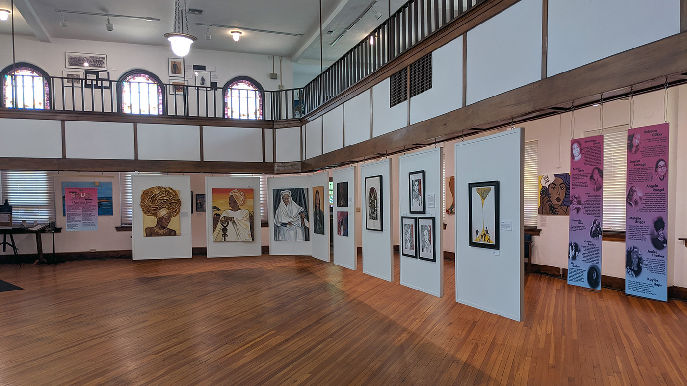 The main gallery of The Kansas African American Museum, where art work is displayed on hanging panels.