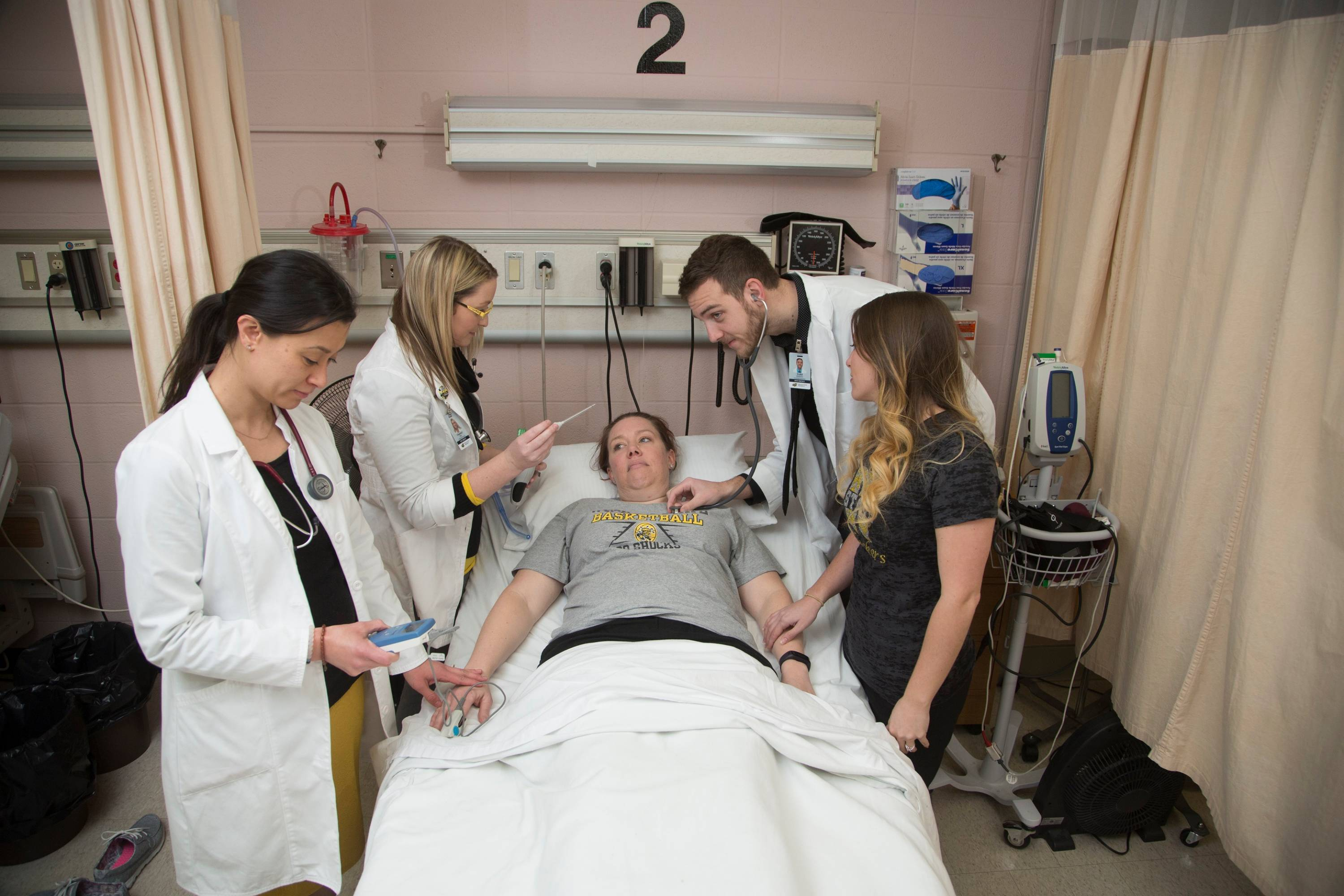 Nursing students checking patient