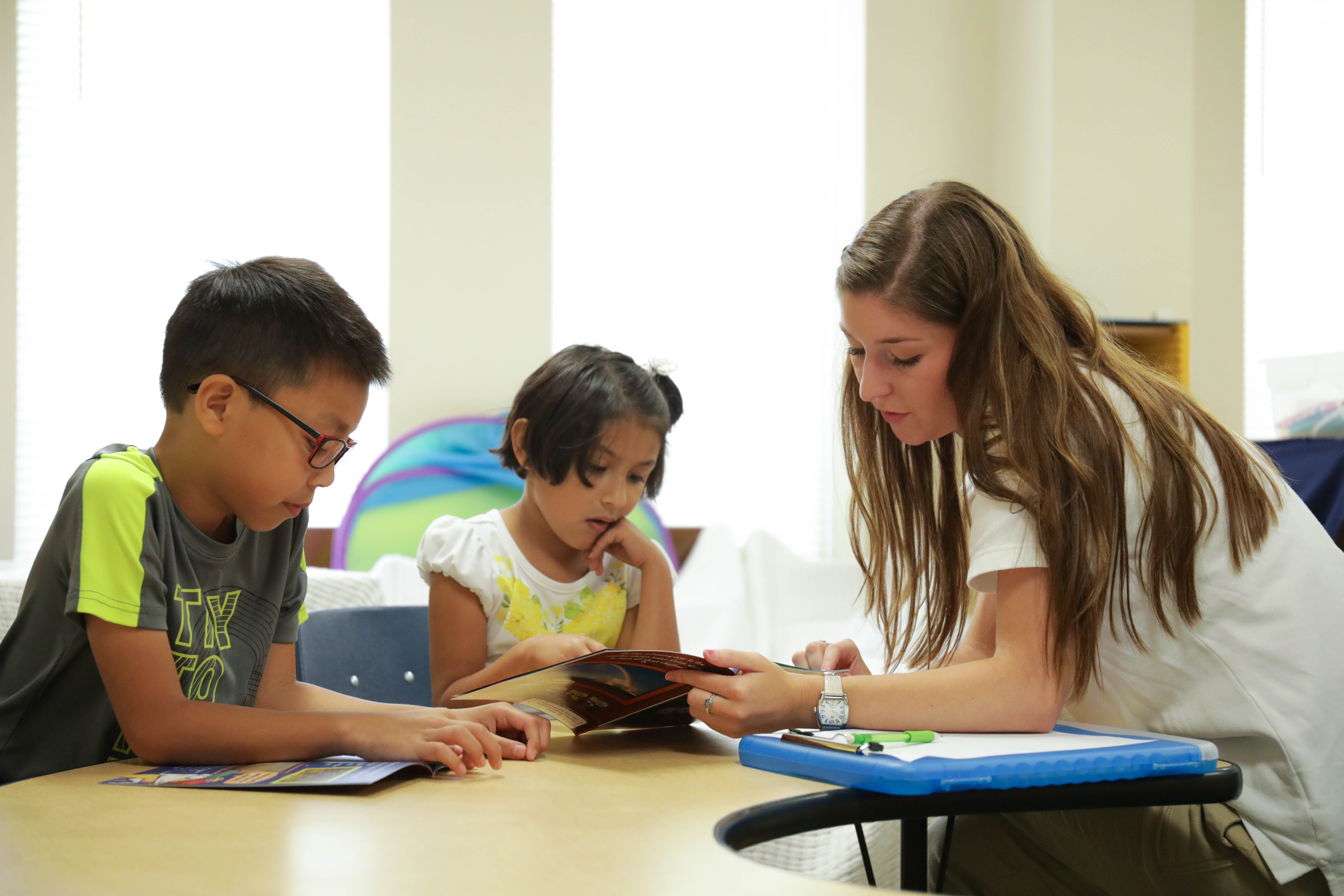 Speech-Language graduate student helping children with literacy skills