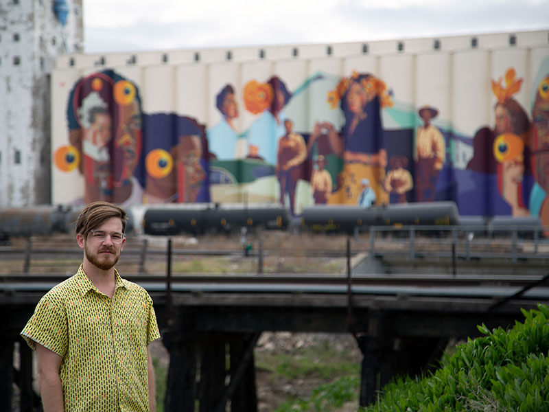 Art History and Honors College student Dale Small, pictured with the community mural he art directed
