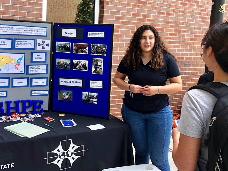 Melissa Rocha, a biomedical engineering major and officer in Society of Hispanic Professional Engineers, tries to get fellow students to join at Engineering Block Party held the first week of school.