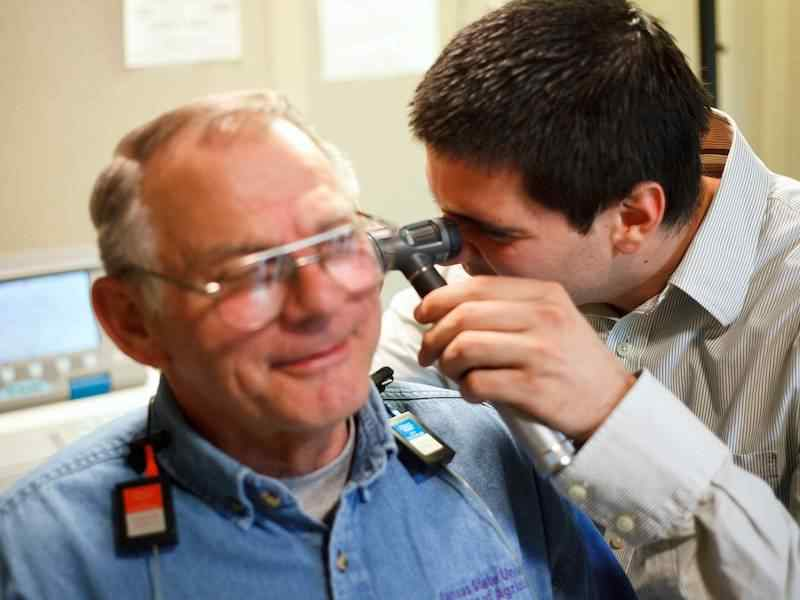 WSU student looking into an older male patient's ears.