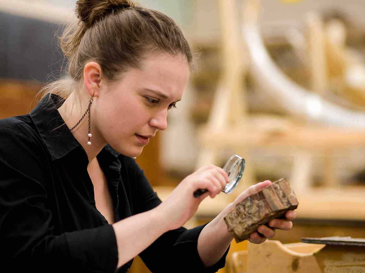 Female student examines a rock specimen