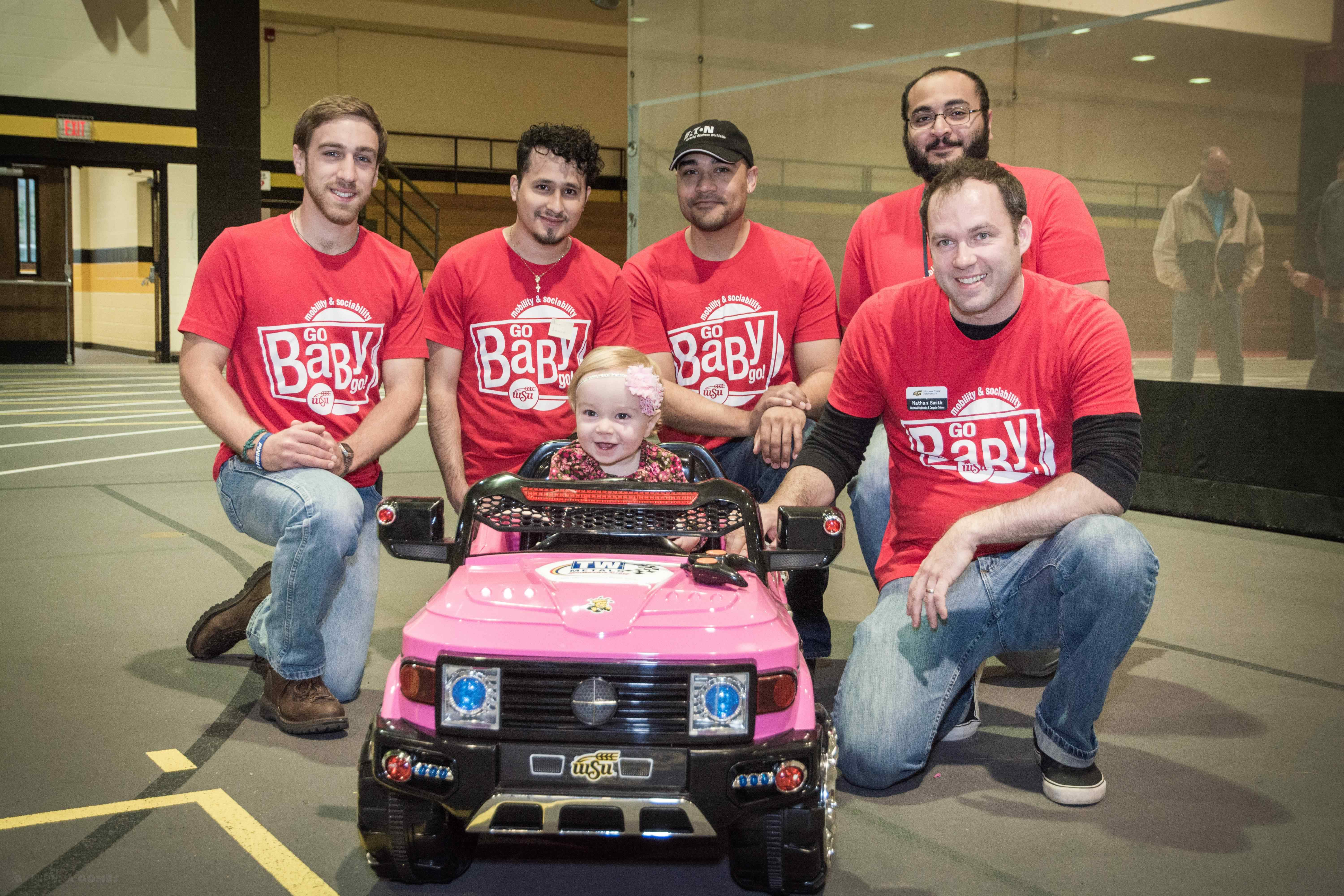 Engineering students pose in front of electric car for Go Baby Go.
