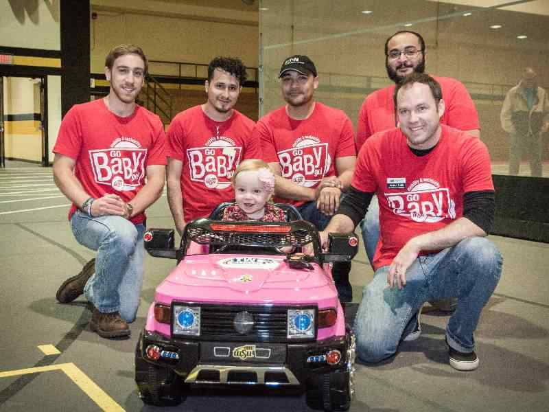 Mechanical Engineering students pose by electric car for Go Baby Go.