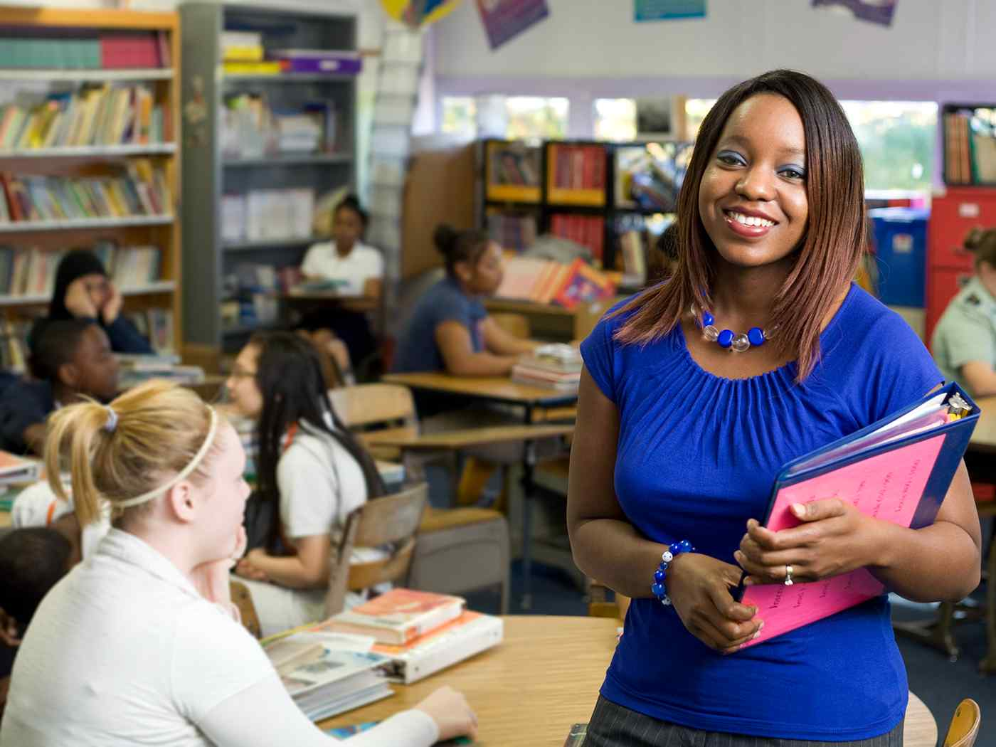 Female student teacher in middle school classroom.
