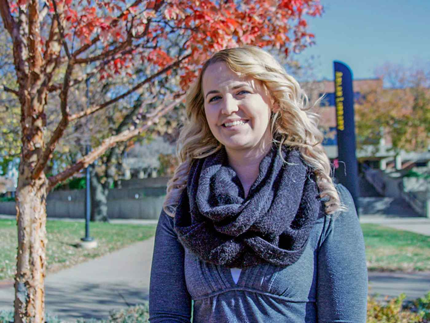Female psychology student photographed smiling during the day on campus.