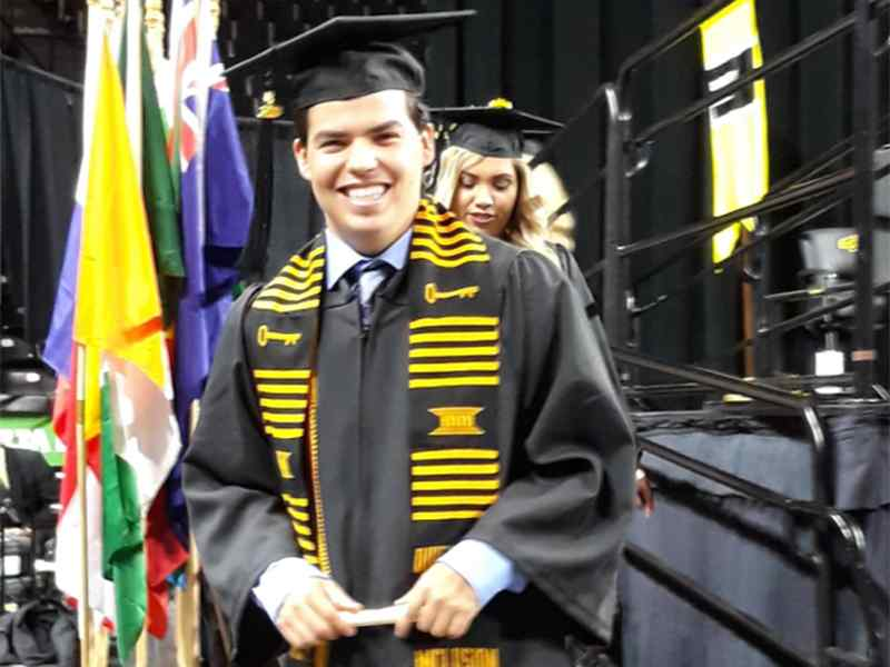 A graduate crosses the stage with his Spanish degree at commencement