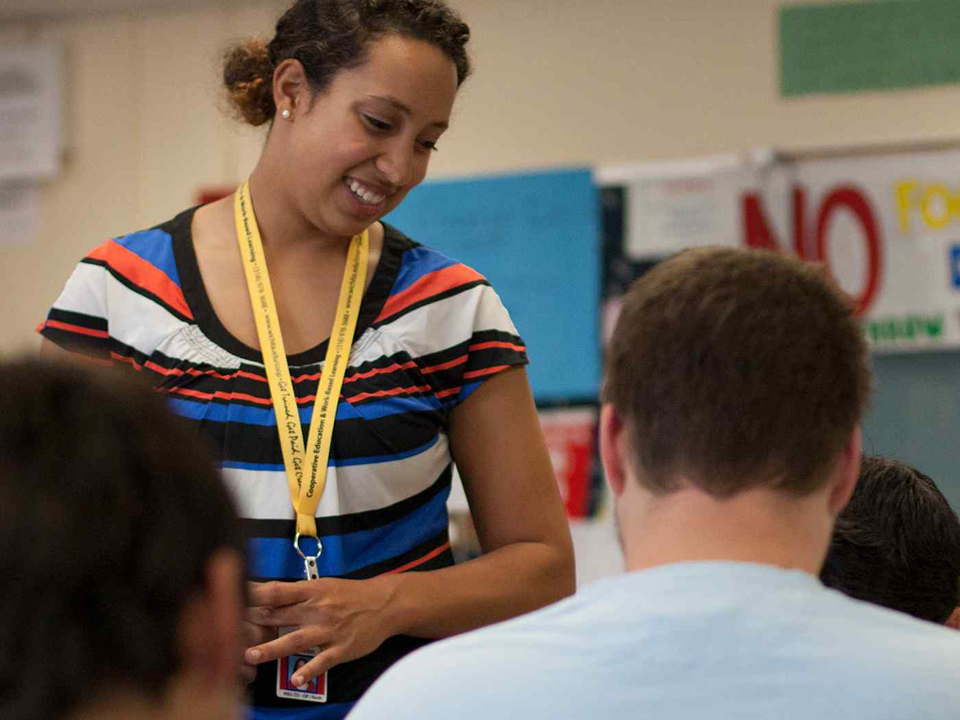 Female student teacher smiling in classroom.