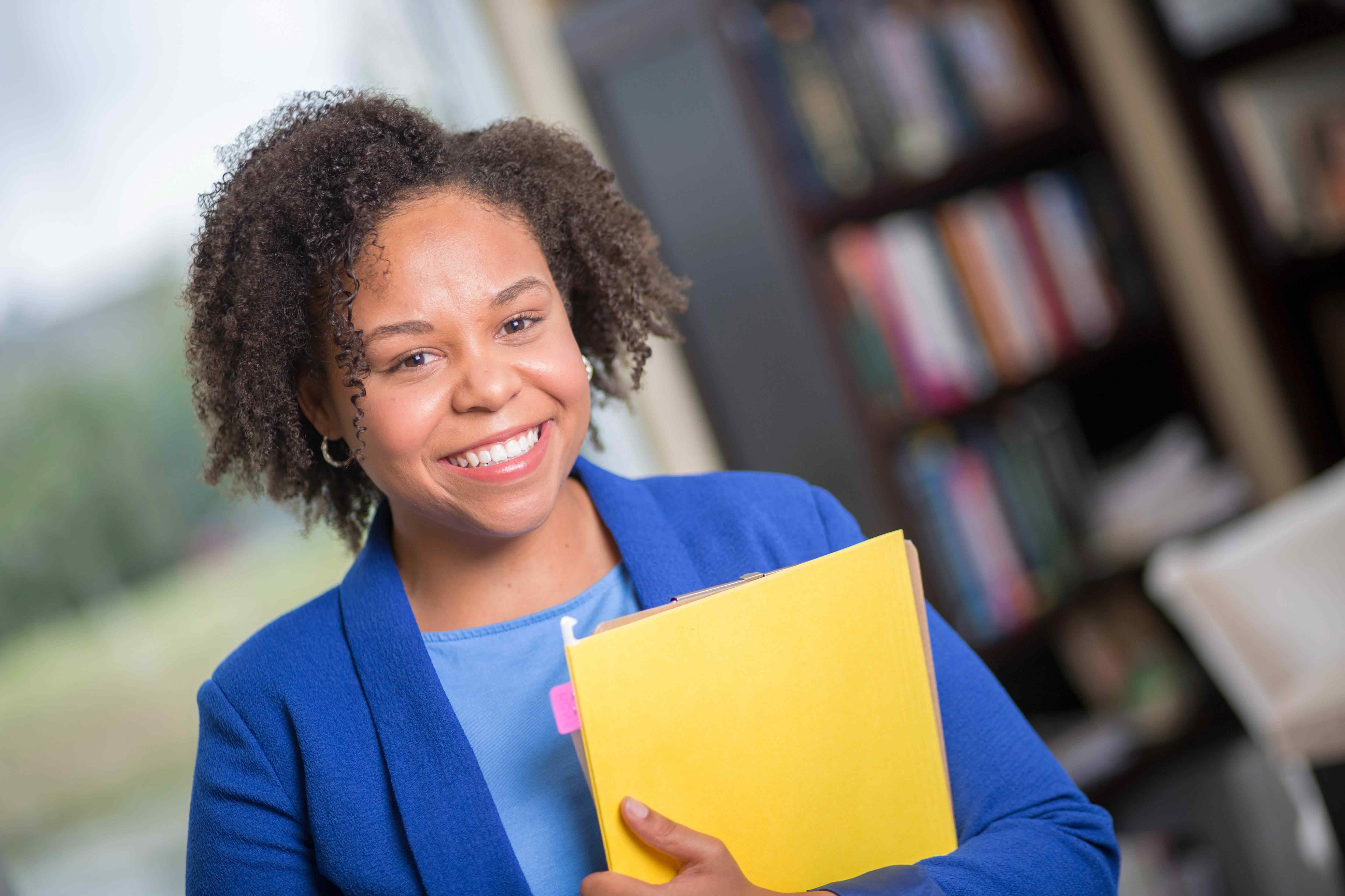 Female business student smiling and holding files.