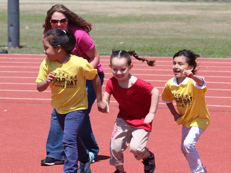Student teacher running with elementary class.