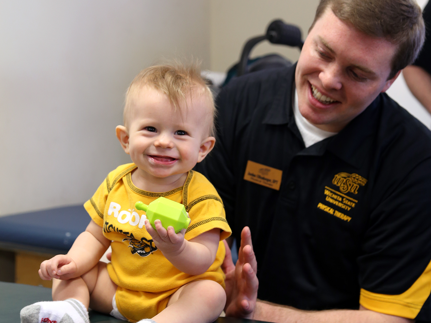 Baby smiling while playing with male WSU student.