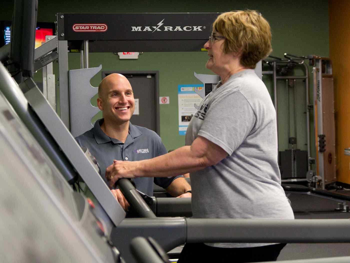 Older woman with trainer on treadmill.