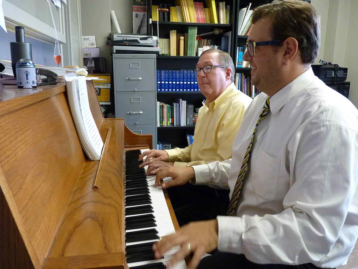 Professor teaching a student on the piano.