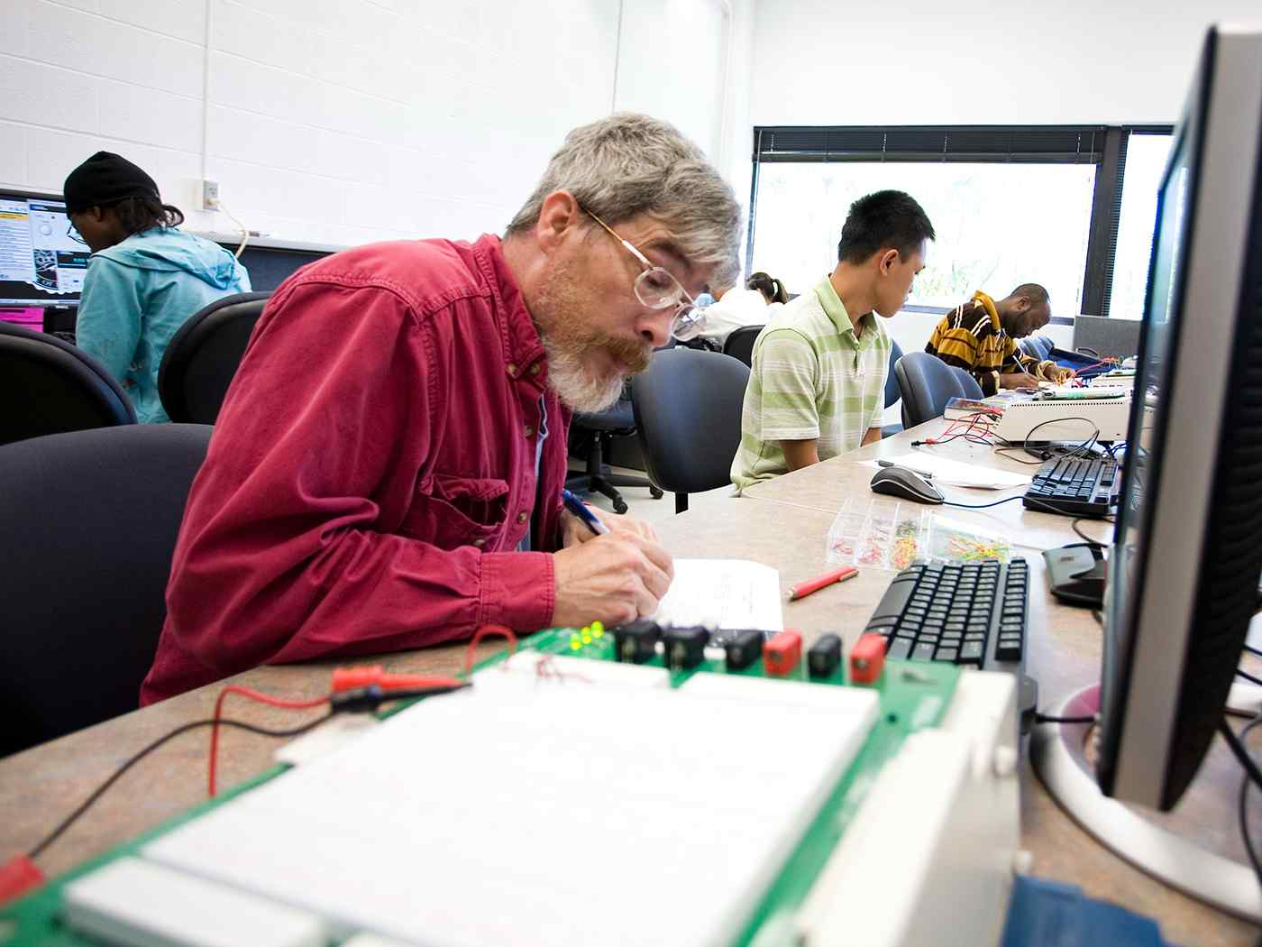 Older graduate student working on a circuit unit.
