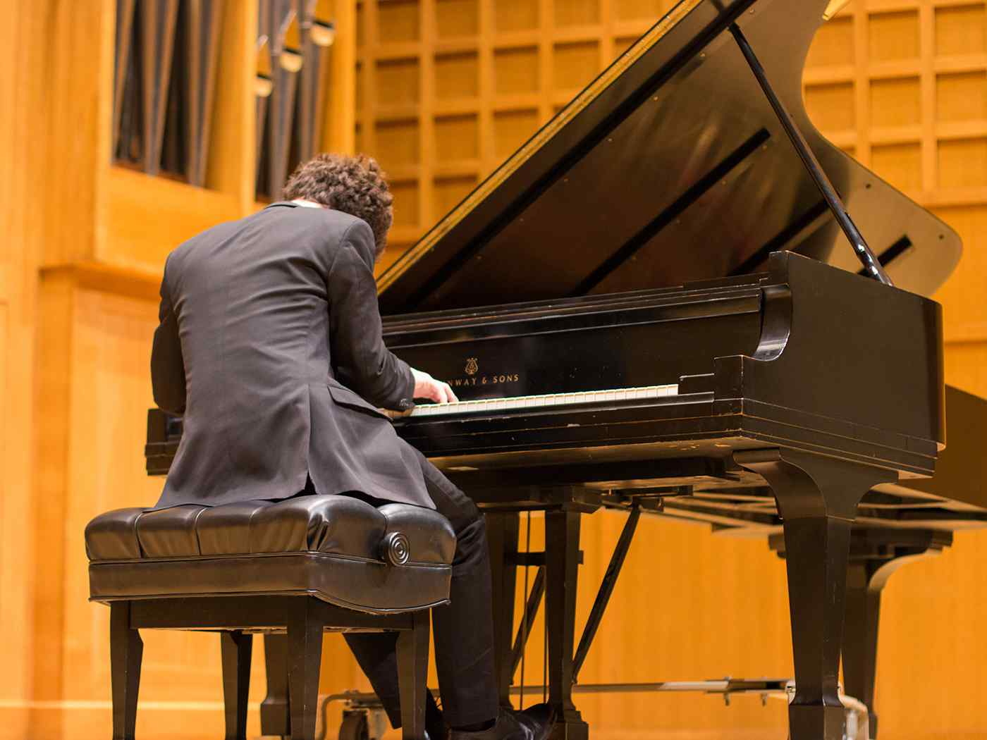 Male pianist plays in Wiedemann Hall